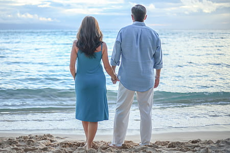man and woman standing on shoreline while holding hands
