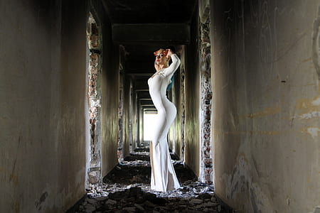 woman with white long-sleeved bodycon slit maxi dress standing on hallway