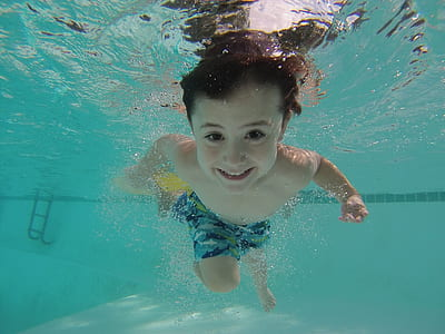 boy in blue shorts swimming on pool during daytime