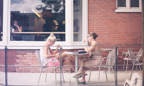 two women sitting on patio dining set beside brown concrete house