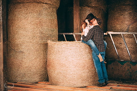 man and woman kissing on hay