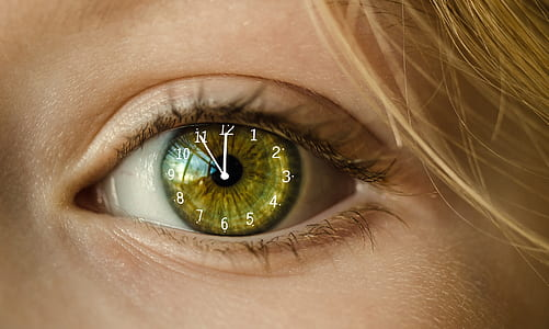 close up edited photo of woman's left eye with analog clock