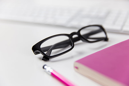 Reading glasses on a white office desk with computer keyboard, notepad and pencil