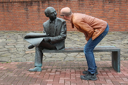 man wearing brown jacket looking at the statue
