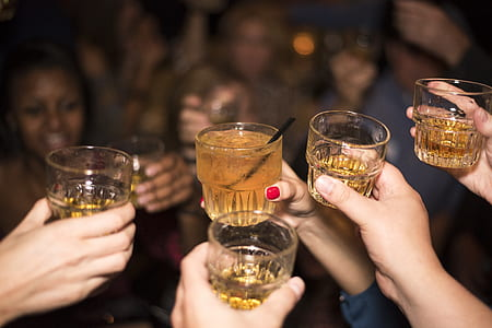selective focus photography of person holding shot glasses