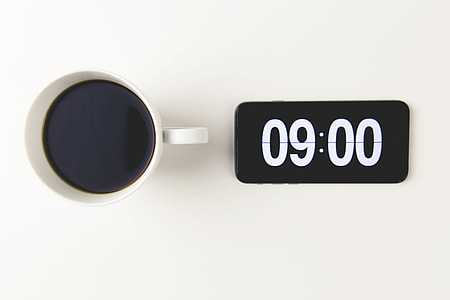 Cup of coffee with the time displayed on mobile iPhone smartphone clock