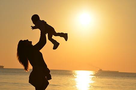 silhouette lifting her baby upward near sea during sun set