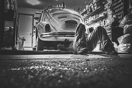 grayscale photo of Volkswagen Beetle and man