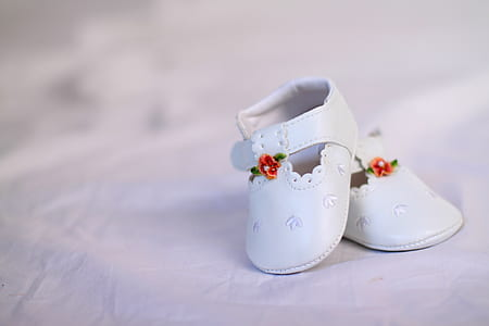 pair of baby's white shoes on white textile