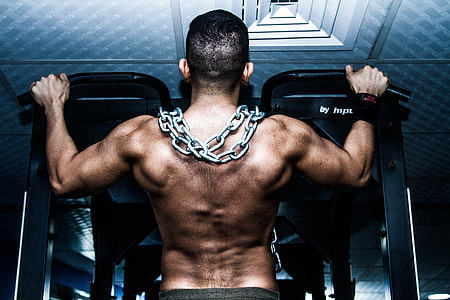man pull his self on black pull up bar with chains on his shoulder