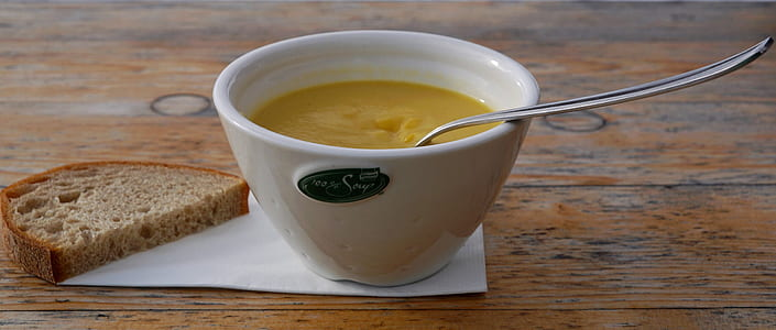 photo of white ceramic bowl of soup and bread