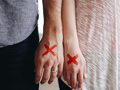 man and woman wrote X mark on their hands