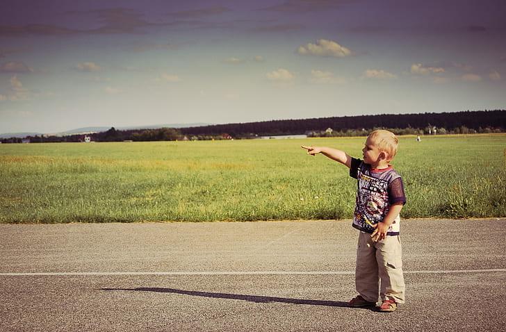 boy standing at pathway raising right hand