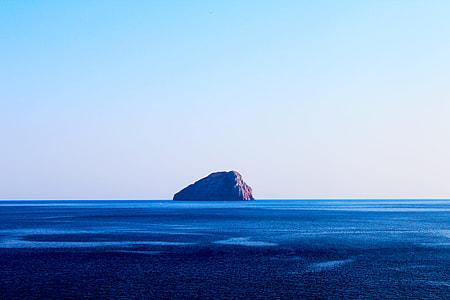 island between on calm body of water