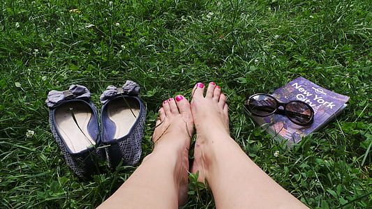 person's feet beside flat shoes