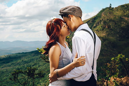 man and woman kissing and view of mountain