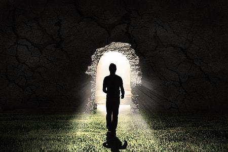 silhouette of man walking towards broken wall showing light