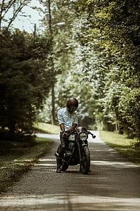 man wearing full-face helmet while riding motorcycle on asphalt roadway between trees during daytime