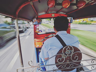 time lapse photography of man wearing white collared shirt inside auto rickshaw ruding daytime