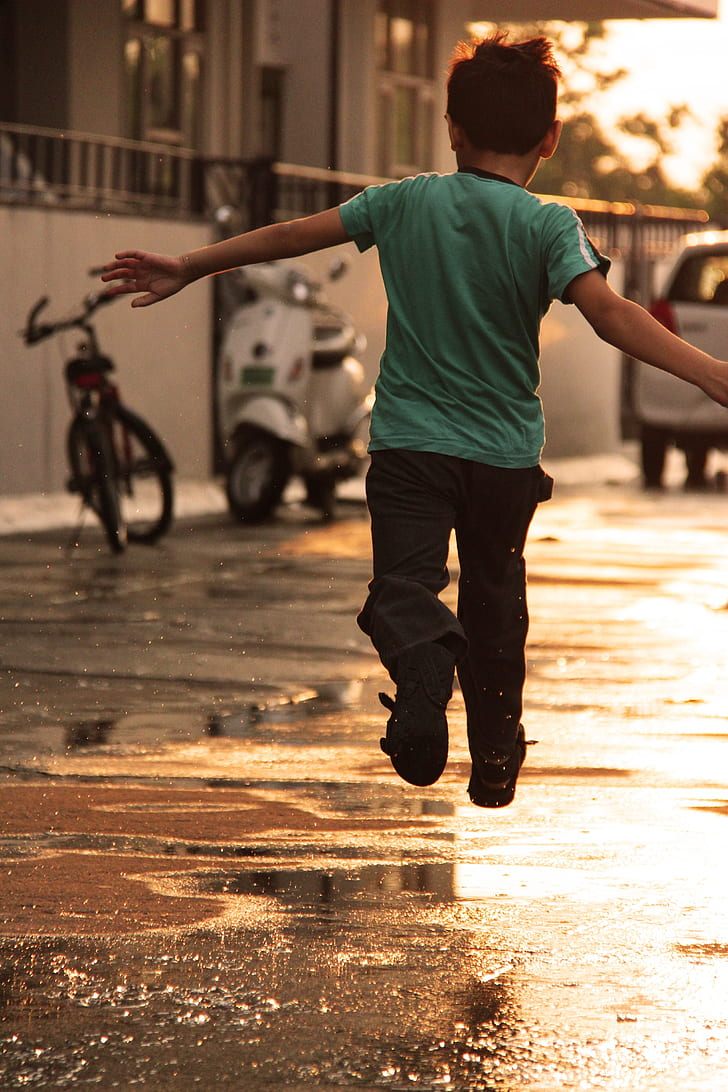 boy in teal t-shirt and black pants jumping on road