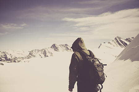 photo of person with hiking backpack on mountains filed with snow