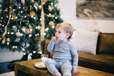 baby wearing gray long-sleeved shirt and pants sitting on brown wooden coffee table