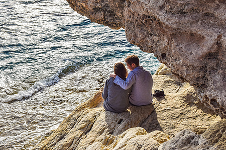 couple sitting on cliff during daytime