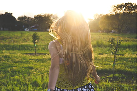 blonde-haired woman walking on green grass field