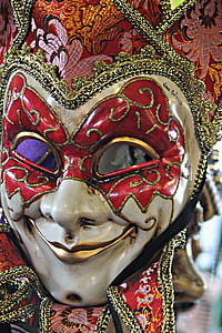 shallow focus photography of red and white venetian mask