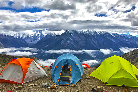 three dome tents with background of mountains during golden hour