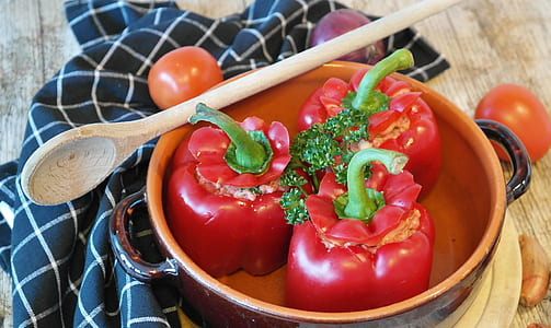 three red bell peppers in bowl with wooden spoon on table