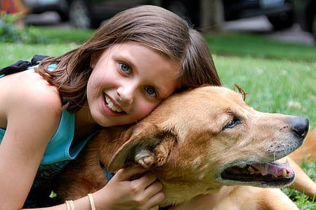 girl wearing green sleeveless shirt lying on short-coated brown dog