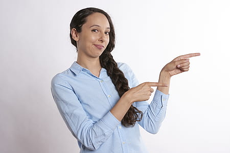 woman wearing blue dress shirt pointing to her left