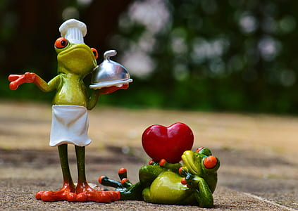 bokeh shot of two green chef frogs figurines