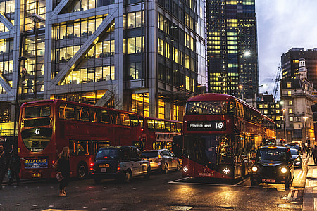 Traffic of taxis, buses and cars on the streets of London at sunset