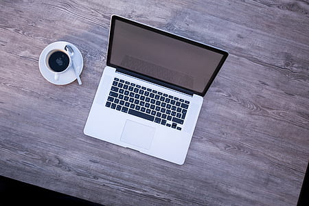 MacBook beside white coffee cup