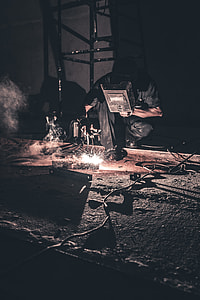 man holding welding mask while welding