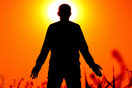 silhouette of person standing on grass field in front of orange sunset