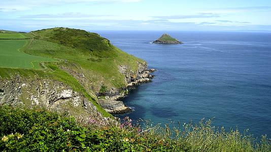 landscape photo of hill near body of water