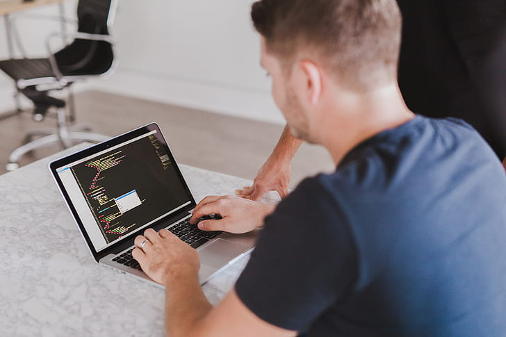 man typing on macBook Pro