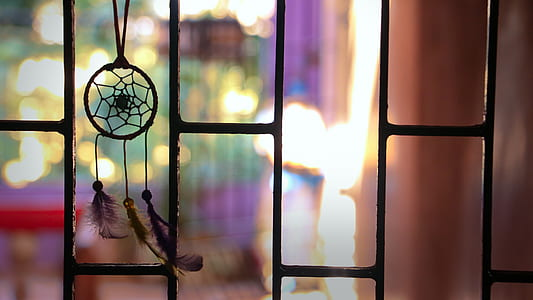 photo of dream catcher near window grille