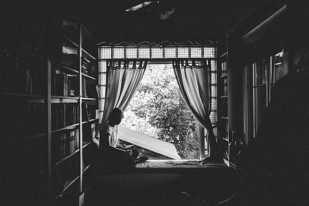 grayscale photo of man sitting near open window