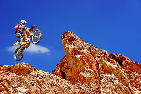 person on dirt bike jumping off from cliff