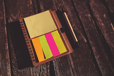 yellow, pink, and orange sticky notes on brown notebook