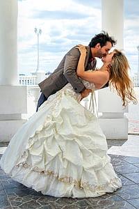 man and woman kissing near white concrete pillar during daytime