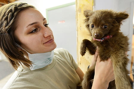 girl with mouth mask holding a gray puppy