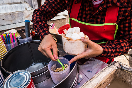 Serving fresh coconut ice cream in young coconut
