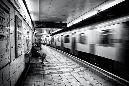 A woman waits on the platform as the train arrives on the London Underground