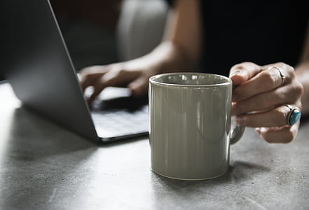 person using laptop computer about to reach ceramic mug