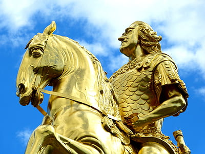 gold-colored man riding on horse statue